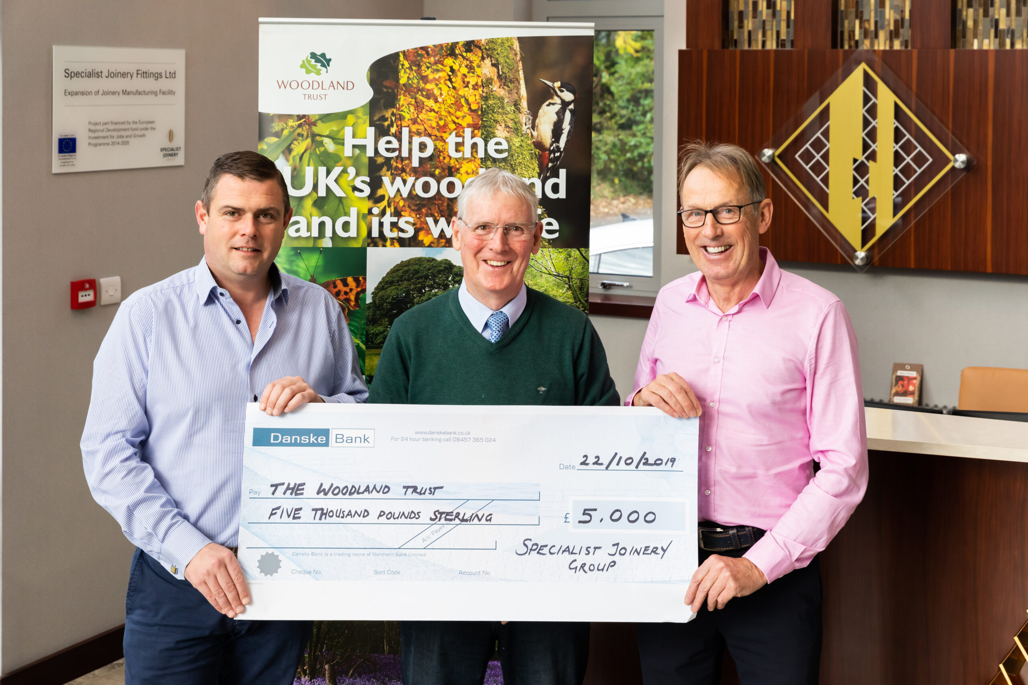 Ciaran O'Hagan and JB O'Hagan presenting a cheque of £5,000 to the Woodland Trust
